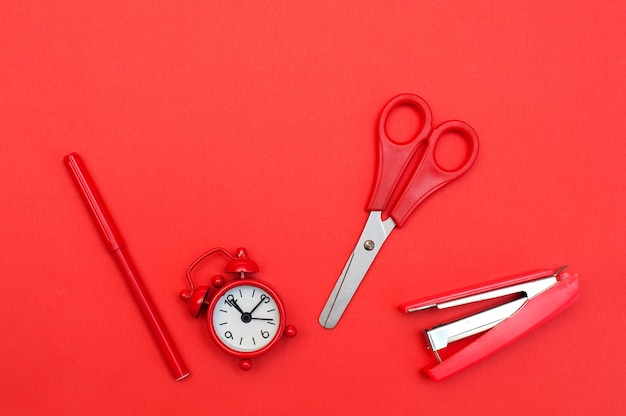 Красный будильник и школьные принадлежности на красном фоне