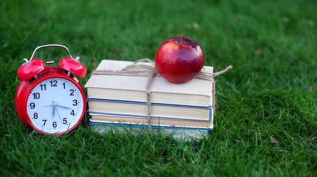 Красный будильник и стопка старых книг в парке