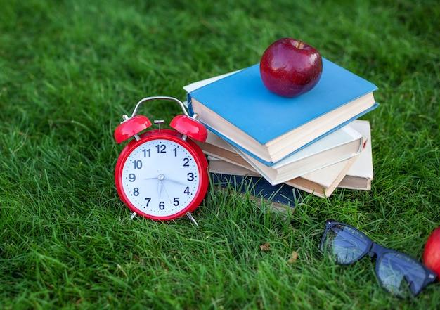 Красный будильник и стопка старых книг в парке осенним утром