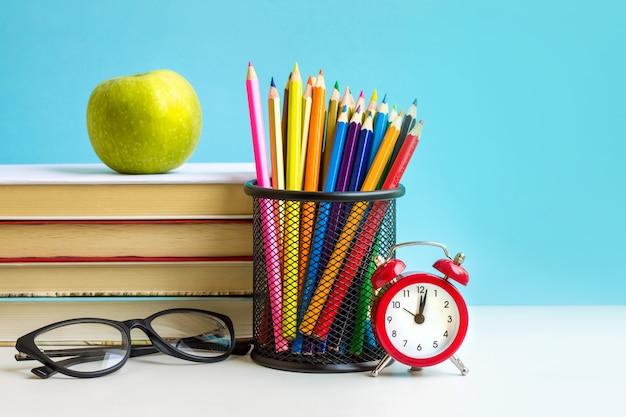 Red alarm clock, apple, color pencils, books on blue