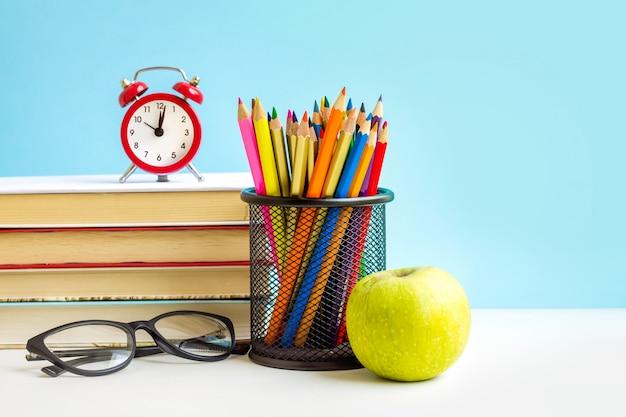 Красный будильник, яблоко, цветные карандаши, книги на синем