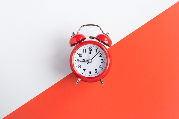 Red alarm clock on the bicolor background.  top view. copy space. closeup.