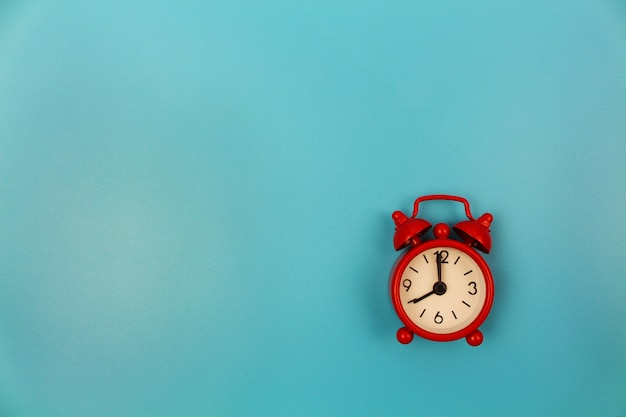 Red alarm clock on blue background. top view. flat lay.