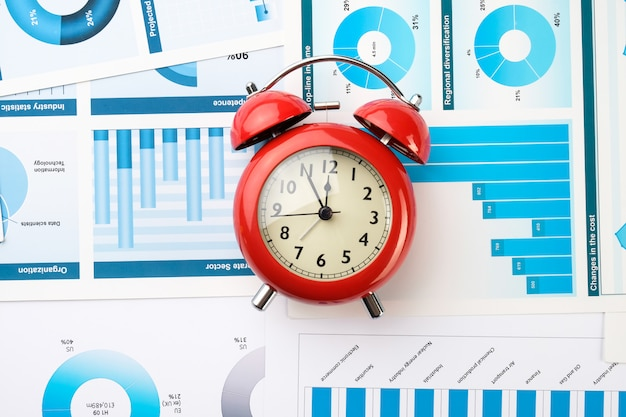 Red alarm clock on business charts. business development concept.