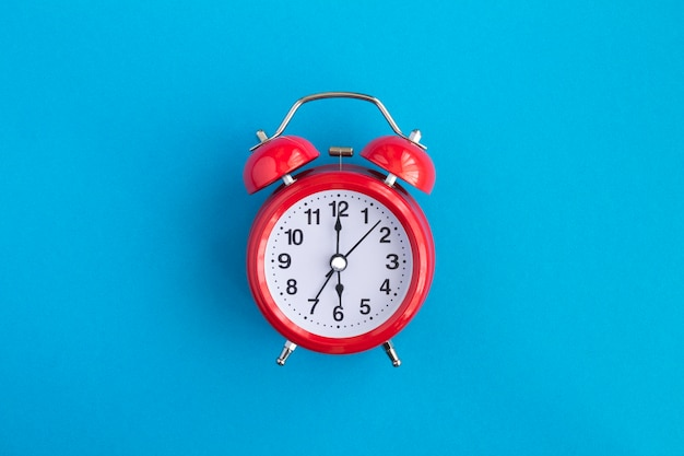 Red alarm clock in the center of the blue background