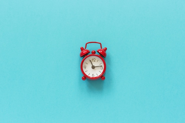 Red alarm clock in center on blue paper background.
