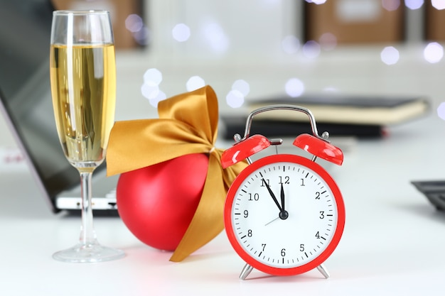 Red alarm clock and champagne goblet at office table