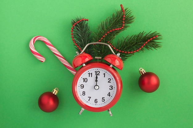 Red alarm clock and christmas composition on the green background. top view. copy space.
