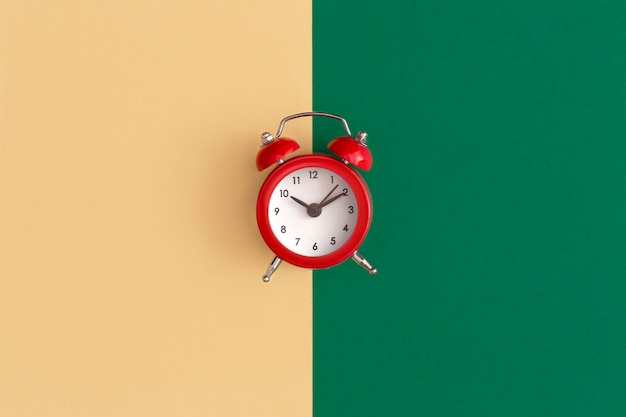 Red alarm clock on color background