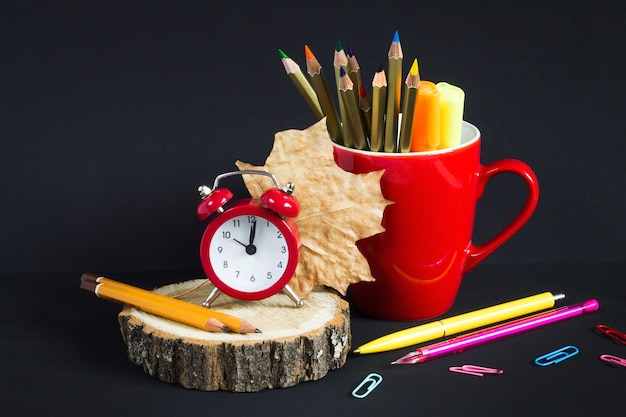 Red alarm clock, color pencils, books and maple leaf on a black wooden background.