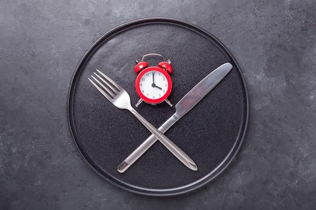 빨간색 알람 시계, 포크, 나이프와 어두운 돌 배경에 빈 블랙 세라믹 접시. 간헐적 단식 개념-이미지