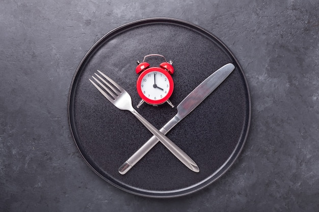 Red alarm clock, fork, knife and empty black ceramic plate on dark stone background. intermittent fasting concept - image