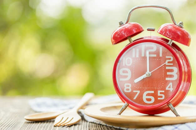 Red alarm clock, fork, and spoon on wooden table with green outdoor nature blur  eight o'clock, time for eating concept