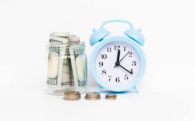 Red alarm clock, glass jar and coins on table against wooden background. money savings.