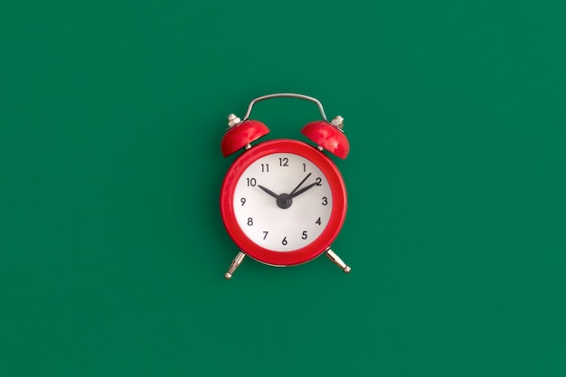 Red alarm clock on green background