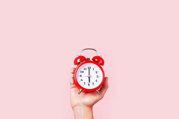 Red alarm clock in hand, on pink background, concept time to get up