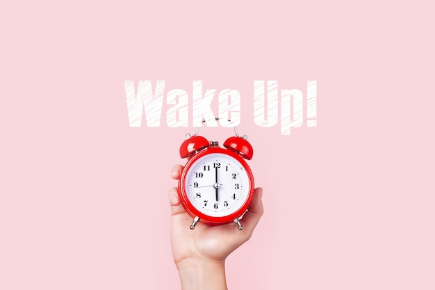 Red alarm clock in hand over pink space,  wake up concept