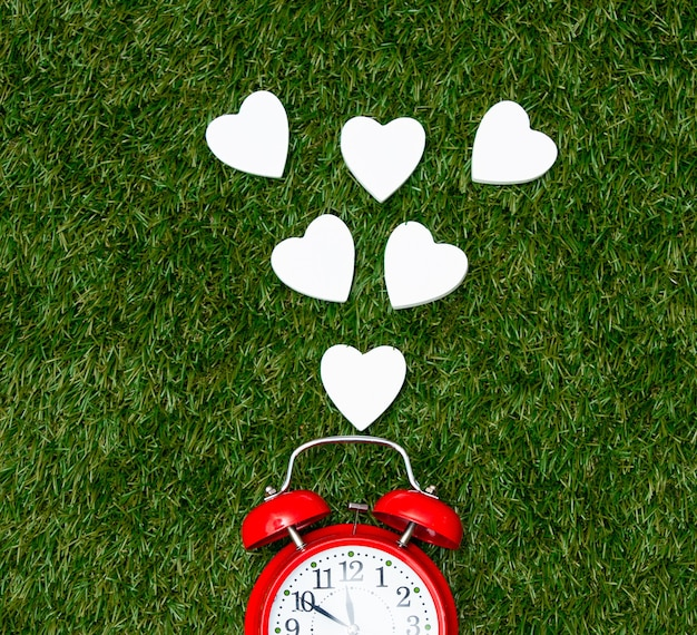 Red alarm clock and heart shapes on green grass.