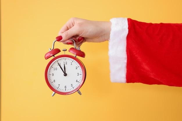 빨간 알람 시계는 산타 클로스 의상 새해와 크리스마스 축하 개념에 손을 잡고