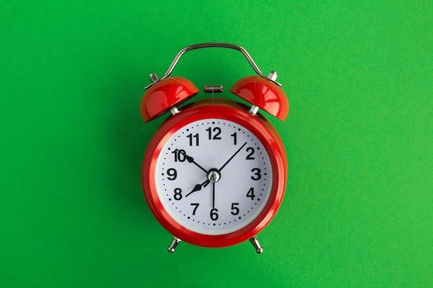 녹색 테이블 중앙에 빨간색 알람 시계. 평면도. 공간을 복사하십시오.