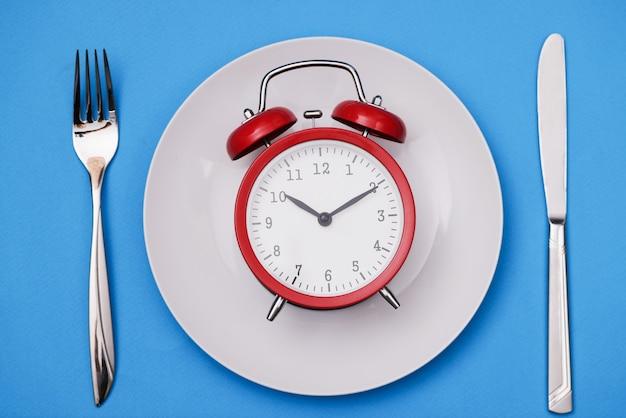 포크와 나이프 옆 접시에 빨간색 알람 시계 거짓말