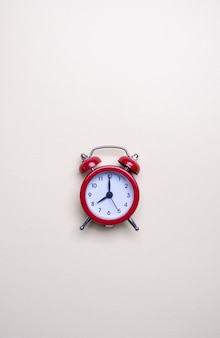 Red alarm clock on light pastel background. blank note for text. reminder. space for copy. minimal concept.
