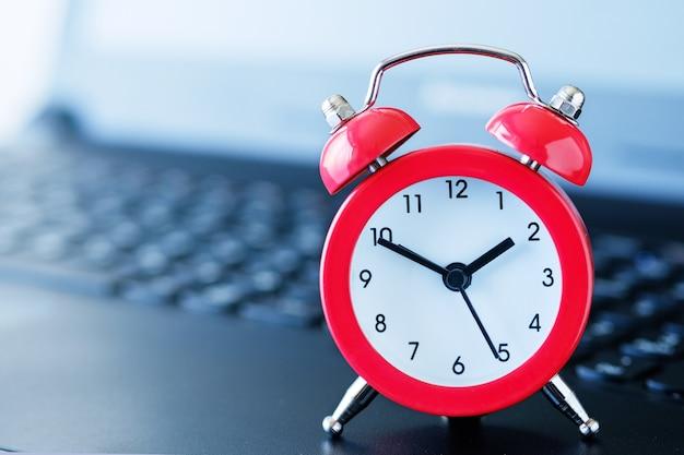 背景がぼやけ、被写界深度が浅い、コンピューターのキーボードの赤い目覚まし時計。