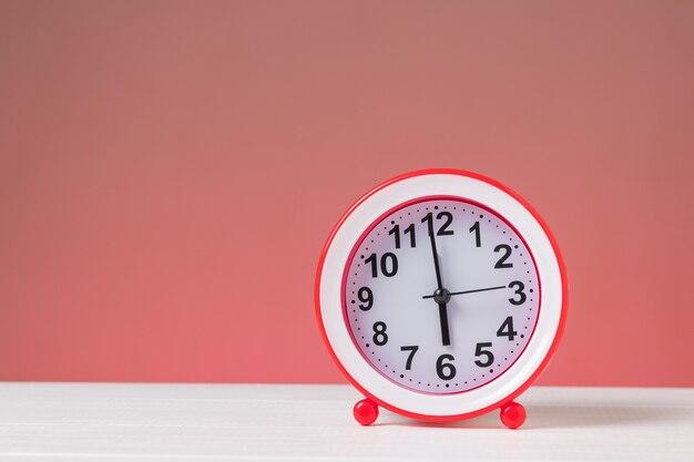 Красный будильник на белом столе на красном фоне. классические аналоговые часы.