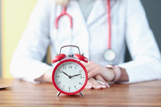 흰색 코트에 의사의 배경에 빨간색 알람 시계. 의료 보험 개념