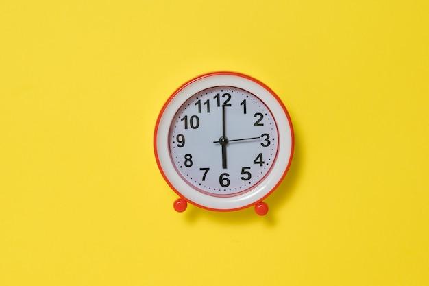 Красный будильник на ярко-желтом фоне. классические аналоговые часы.