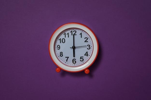 Красный будильник на темно-желтом фоне. классические аналоговые часы.