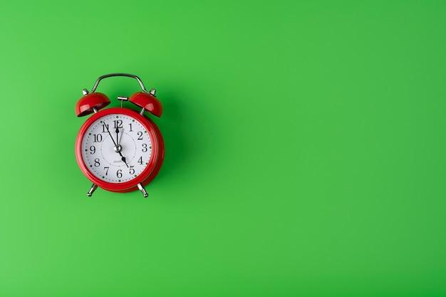 緑の色の背景に赤い目覚まし時計緑の背景に配置された赤い目覚まし時計の画像