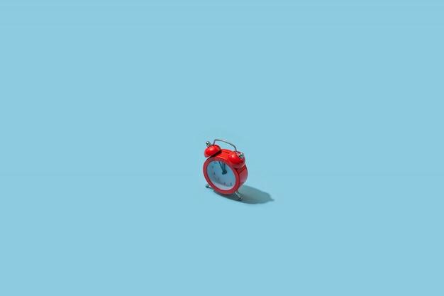 Красный будильник на пастельной голубой предпосылке. креативная идея. минимальная концепция изометрические, резкий свет