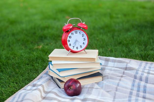 Красный будильник на стеке старых книг и яблоко в парке осенним утром