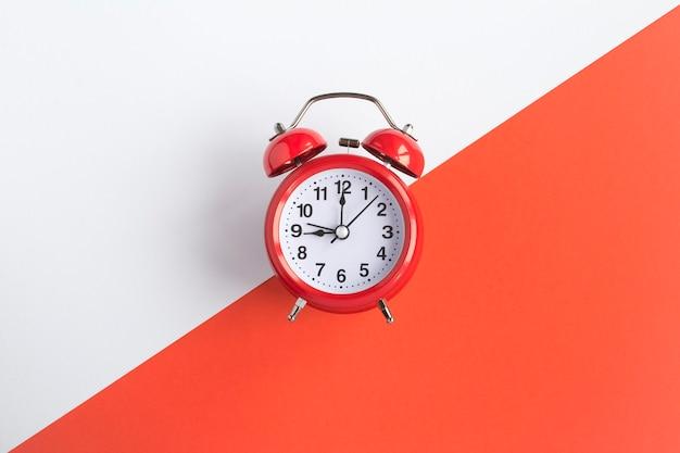 二色の背景に赤い目覚まし時計。上面図。スペースをコピーします。閉じる。