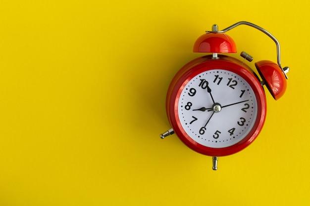 노란색 바탕에 빨간색 알람 시계입니다. 평면도. 공간을 복사하십시오.