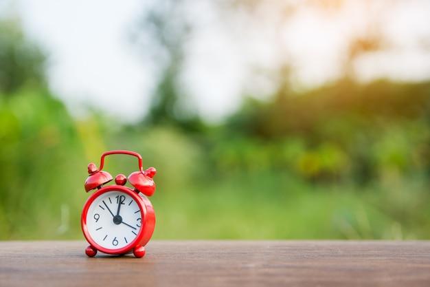 ぼかし自然の背景とコピースペースと木製のテーブルに赤い目覚まし時計