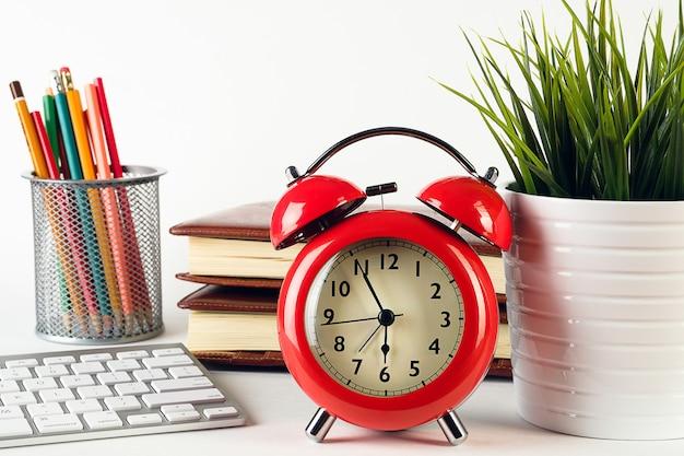 デスクトップ上の赤い目覚まし時計、鉛筆、コンピューターのキーボード、ノートブック。
