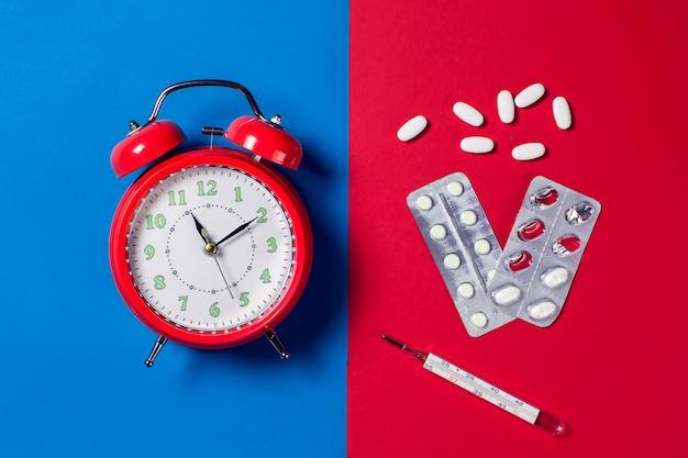 Красный будильник, таблетки и термометр на цвет фона. концепция здравоохранения и медицины
