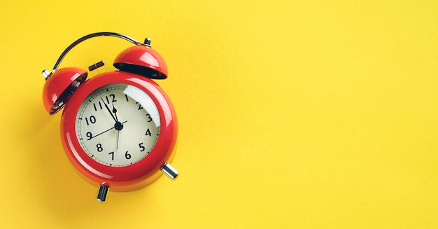 Red alarm clock in retro style on a bright yellow background. banner.