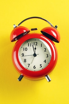 Red alarm clock in retro style on a bright yellow background