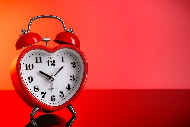 Red alarm clock in the shape of a heart