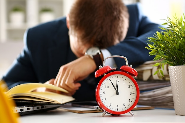Red alarm clock shows late time closeup and tired office male clerk in suit take nap on table workplace full of exam papers.
