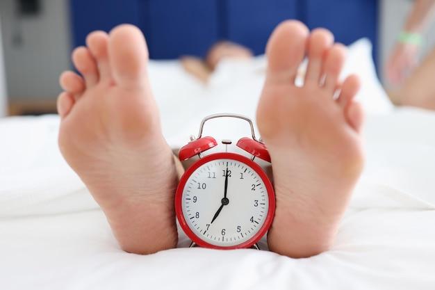여성 발 뒤꿈치 사이에 침대에 서 있는 빨간 알람 시계는 조기 각성 개념을 닫습니다