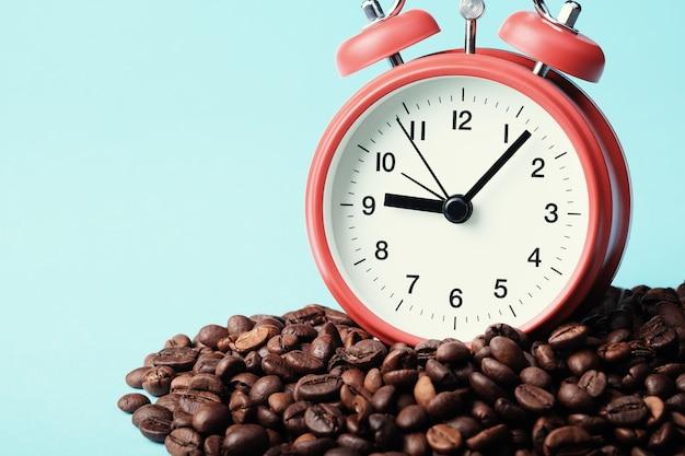 コーヒー豆の山に立っている赤い目覚まし時計。朝の目覚めの概念、就業日の始まり