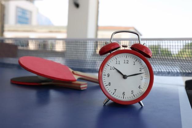 스포츠 개념을 위한 라켓 근접 촬영 시간 근처 테니스 테이블에 서 있는 빨간색 알람 시계