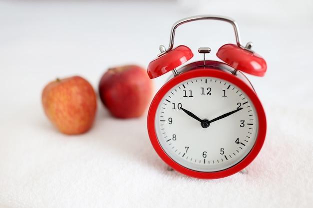 사과 근접 촬영 근처 하얀 수건에 빨간 알람 시계 서. 건강한 라이프 스타일 다이어트 개념