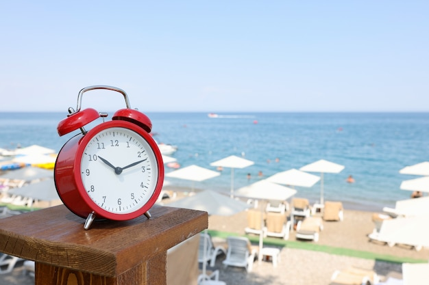 Red alarm clock standing on sea beach of hotel closeup. entertainment schedule in hotels concept