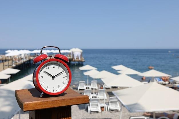 빨간색 알람 시계는 해변과 바다 여름 시간 휴가 개념의 배경에 서 있습니다