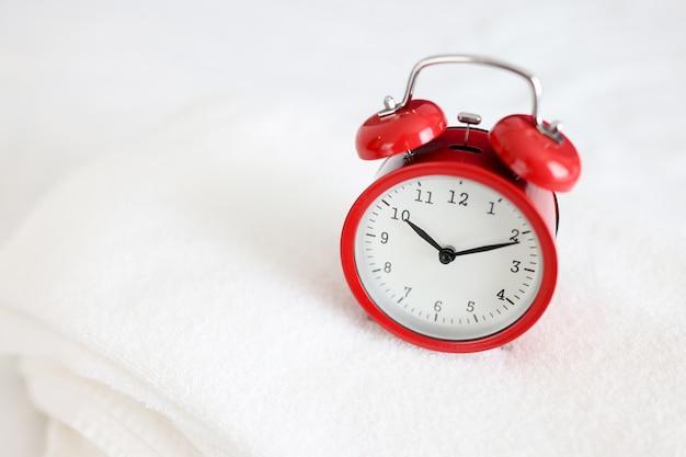 빨간색 알람 시계는 매일 아침 샤워 컨셉으로 하얀 수건 위에 서 있습니다.